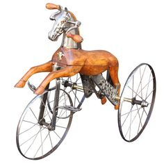French Velocipede or Child's Tricycle /  c.1870 /  a body of carved wood with brushed steel faceplate and glass eyes, resting on spoke wheels with brass accoutrements and horse-hair tail / this is amazing...