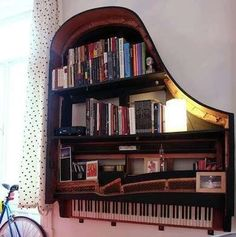 Grand Piano Bookshelf  What do you call a grand piano with no legs or innards? How about a distinctive wall-mounted shelving unit! Books, candles, family photos, and even a lamp populate the shelves of this unique city apartment creation. You'll definitely want to make sure you've got this baby mounted to the studs!