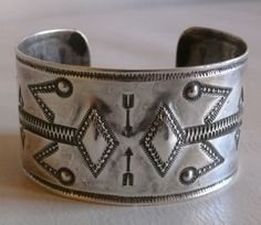 An exceptional hand-hammered and repouseed ingot-silver Navajo cuff bracelet with stylized Yei pictorials, circa 1920's-1930's