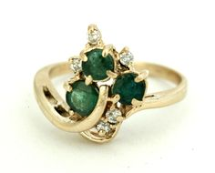 VINTAGE EMERALD AND DIAMOND RING.  Yellow gold cluster mounting with three round emeralds and five round diamonds.