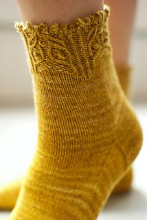 This sock with its ornate cuff, and simple leg and foot, is perfect for showing off beautiful gradient yarns. KnitCircus Thrilling yarn comes divided…