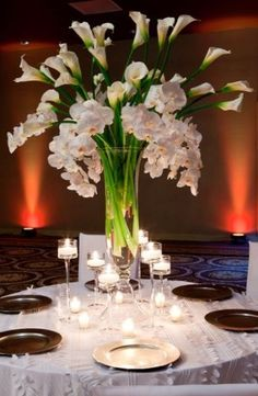 Tall, slender vases display white calla lily's and white orchids. Silver and black chargers are illuminated by small and mid-size tea candles. Elegant sophistication.