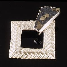 """Arline Fisch    Tumbling Squares brooch, 1996  Plaited, sandblasted sterling, pyrite in schist.  3"""" W x 3.5"""" H"""