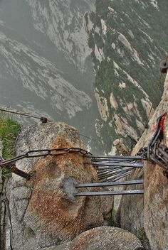 Hua Shan Cliffside Plank Walk   As you hike the five mountain peaks, one of the options is to take the Cliffside Plank Path. First, climb straight down a crevice in the mountain with nothing below but other peaks and the valley floor far below.