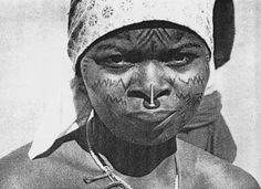 Makonde women with ndona (labret), forehead,  chin, cheek, and sternum tattoos. The labret is  made of black ebony with an upright needle passing close to the nose, a sign that the girl is of marriageable age. Photograph ca. 1960. Makonde - by John Stone