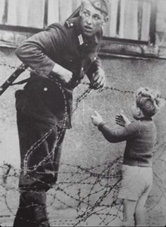 An East German soldier helping a boy cross the newly formed Berlin Wall -1961
