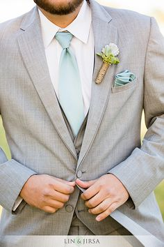 Dana point yacht club wedding, light gray wedding suit, summer wedding tuxedo, groom buttoning jacket heather grey allure suit with light blue long tie with matching pocket square and white boutonniere