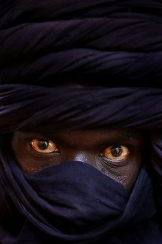 A Tuareg nomad man arrives into the town of Tombouctou, Mali (West Africa) by camel for supplies. The Tuareg people are descended from Berbers in the region now known as Libya.