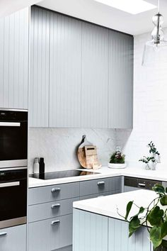 grooved grey cabinetry, white marble benchtop and splashback.