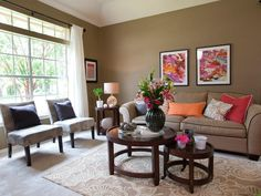This lively living room features an all-over earthy taupe color with pops of color sprinkled throughout. Bright pink and orange pillows decorate the sofa, while a neutral floral rug is situated under two round coffee tables.