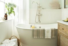 Pedestal tub with traditional exposed shower and tub.  Bead board, vanity with louvered doors, subtle colors.