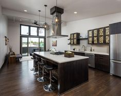 Dark wood cabinets and floors and black accents come together for a sleek and formal look in this spacious, modern kitchen. Striking, modern pendant lights and mosaic-tiled cabinets are eye-catching touches in this classy, urban space.