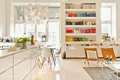 A Finnish home decorated in the Scandinavian spirit. White on white, design classics and some colour via the bookshelf. All open plan