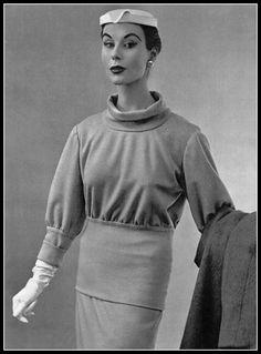 Myrtle Crawford in two-piece gray jersey sweater which falls very low on the hips over a wide band of soft jersey, by Balenciaga, photo by Pottier, 1953