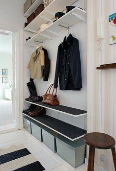 sol en planchers blancs et tapis à rayures blancs et noirs, papier peint en beige pour l'entrée, chaise d'entrée en bois marron foncé
