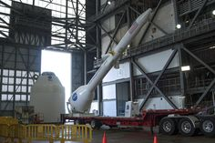 A crane lifts a replica Launch Abort System off its trailer so it can be placed atop a mockup Orion capsule
