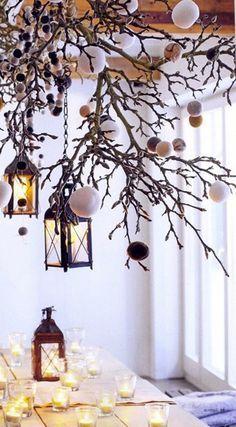 Une suspension faite de branchage et de guirlande de pompons à accrocher au dessus de la table de Noël