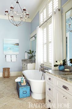A soaking tub rests between a pair of matching vanities in a cool blue bathroom. - Photo: Jean Allsopp / Design: Georgia Carlee