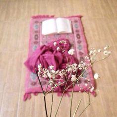 Open book of Quran on pink prayer mat