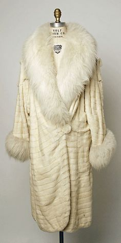 This is a clutch coat from the 1920's. This is a large, cocoon-like coat and is clutched by a pin holding it in place. This necessity to hold the dress closed or use a pin causes a sort of pose for women when they went this garment.