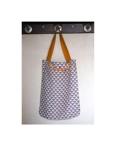 Ce sac en coton imprimé graphique sera très pratique car il se range dans sa petite pochette pour se glisser dans votre sac à main. Il vous permettra de transporter vos petites courses et vos divers achats lors de vos séances shopping !  Le sac est en coton imprimé triangle blanc et taupe. Il est cousu avec la technique des coutures anglaises pour de jolies finitions à lintérieur du sac. Les anses sont couleur jaune moutarde, et sont doublées, elles sont fixées au sac par une couture en…
