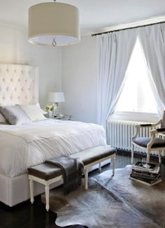 Sophisticated white & gray bedroom design with white tufted wingback headboard, gray silk pillow, glass lamp, French white bench in gray linen fabric, French accent chair in gray linen fabric, white drapes, Jonathan Adler Meurice chrome drum pendant and shiny dark wood floors.
