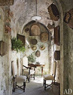 Baskets from Dede's collection hang above Athos's parents' demilune table in the limonaia—traditionally used to store potted lemon trees in winter.