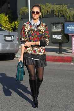 Jessica Alba works the layered look in a MinkPink sweater, collared button down blouse, leather pleated mini skirt, bib necklace, sheer tights, black knee high leather boots, teal handbag, and House of Harlow sunglasses.
