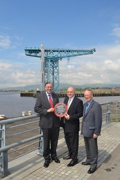 Titan Crane, July 2012.  From left to right John Wood MBE, Chairman of the Institution of Mechanical Engineers' Heritage Committee, Denis Harton, Titan Clydebank Trust Board Members, and Colin Castle, Volunteer Guide, at the Clydebank Titan Crane.