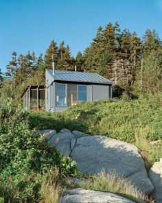 An island house in Maine. See on Dwell. Alex devised a system that takes advantage of ocean views while protecting the cottage from that same northeasterly orientation. The large windows and doors can be shuttered with corrugated aluminum panels.