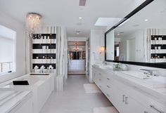 This sleek master bathroom with built in shelving above the bathtub makes every day feel like resort living!