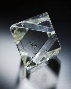 Diamond from Udachnaya-Vostochnaya pipe, Daldyn-Alakit, Sakha Republic, Eastern Siberian Region, Russia _2,5 x 1,9 x 1,9 cm . Main crystal size: 2,5 cm Transparent almost perfect 53.05 carat octahedron with smooth and flat faces, with some slightly modified terminations and inclusions (of flattened sulfide crystals, probably pyrrhotite + pentlandite) in its center. © MIM Mseum , Beirut- Photo by James Elliott