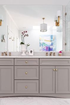 White and gray bathroom features a gray vanity painted Benjamin Moore Chelsea Gray adorned with gold hardware paired with a white porcelain marble like countertop under a frameless mirror illuminated by E.