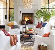 Amelia Wood Bead Chandelier Living Room decor ideas – cozy seating area at fireplace with white slipcovered chairs, pops of blue and red. Amelia Chandelier from Pottery Barn. My Living Room, Living Room Chairs, Home And Living, Living Room Furniture, Living Room Decor, Living Spaces, Cozy Living, Rustic Furniture, Modern Furniture