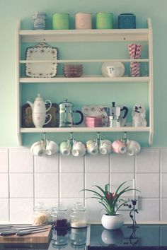 Love the teacups hanging below the shelves, and I spy some Harney and Sons earl grey tea in the corner!