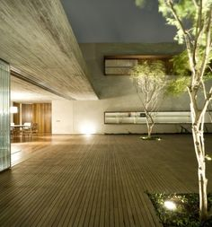 """Residential Architecture: Chimney House by Marcio Kogan: """"..A wooden patio with trees, formed by the volumetry of the house and a concrete wall, articulates the entire program of the Chimney House. The living room is enclosed in the boxed ground floor of this volume and wide windows open it to the external space. The inner dimensions of the living room..create a sensation of coziness, accentuated by the textured of the concrete ceiling made with narrow wooden formwork. In this way, a…"""