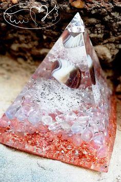 Orgonitová pyramida s velkým tromlem Achátu botswanského, který slouží jako uzemňovací kameny, které nám dodávají citovou, tělesnou a rozumovou rovnováhu.  Dále je obsažen vzácný krystal Aqua Aura /křišťál, jež disponuje extrémně silnými vibracemi. Jak už její název napovídá, dokáže efektivně čistit, uklidňovat a léčit auru. Aqua, Water