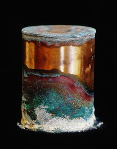"""by David Maisel / cremated remains of mental patients, stored in copper canisters on pine shelves /  """"Over time . . . the canisters have begun to react chemically with the human ashes held inside them; this has thus created mold-like mineral outgrowths on the exterior surfaces of these otherwise gleaming cylinders."""""""