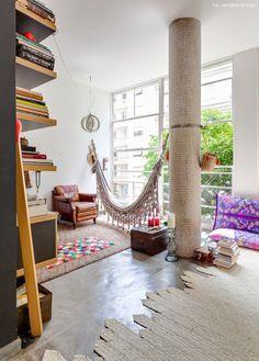Sala de estar iluminada tem cantinho zen com rede de balanço e objetos étnicos.