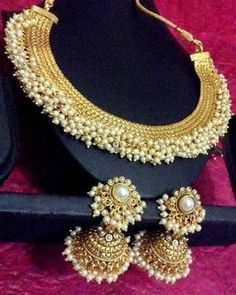 Very pretty and pristine golden necklace set with smiling chandni pearls and very appealing jhumka earrings in the finest traditions of South Indian Temple style jewellry. -https://www.cooliyo.com/product/83815/chandni-pearls-golden-adiva-copper-bridal-necklace-set/