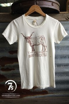 """- """"Trust your neighbor but brand your cattle"""" graphic t-shirt - Black graphic on super soft heather gray tee - Corriente steer with custom Savannah 7s brand on hip - Original drawing by Texas artist -"""
