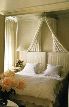 lots of neutral sheer linen, bed crown, headboard is old door, split in two sections and slipcovered.