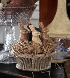 Chalkware bunnies nestled in a bed of wood wool