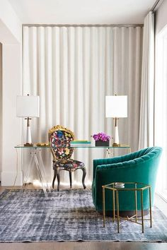 Chic contemporary home office boasts a multi-color French desk chair placed on a black overdyed rug in front of a window dressed in long white pleated curtains and positioned facing a lucite sawhorse desk with a glass top lit by white and gold lamps.