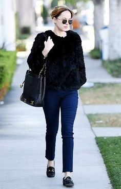 Dakota Johnson wears a fur coat, skinny jeans, Gucci loafers, a vintage Chanel bag, and round sunglasses