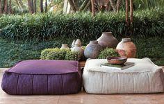 No jardim foi criado um lounge, com pufes da Paola Lenti (Casual Exteriores). Ao fundo, o talude forrado de grama-preta-anã e liríopes. De seu acervo pessoal, o paisagista trouxe os vasos de barro usados no ambiente