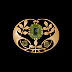 MURRLE BENNETT & Co. (1896-1914) A gold brooch set central peridot and accented with two rectangular peridots. Anglo/German c.1900