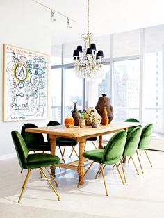 In a Chicago skyrise, Nate Berkus pairs a rustic wood table with midcentury chairs upholstered in green velvet and a crystal chandelier with black lampshades. The combination of styles is both inventive and original. PHOTO: Nate Berkus