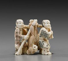 Old carved and polychromed ivory okimono; of two hunters carrying their kill, a ram, between them; L: 2 1/4""