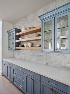 Glass front blue cabinets mounted against gray marble tiles with brass edging flank stacked blond wood floating shelves. Blue Gray Kitchen Cabinets, Shaker Kitchen Cabinets, Glass Front Cabinets, Blue Kitchen Tiles, Stacked Stone Backsplash, Grey Backsplash, Grey Countertops, Grey Marble Tile, Light Grey Kitchens